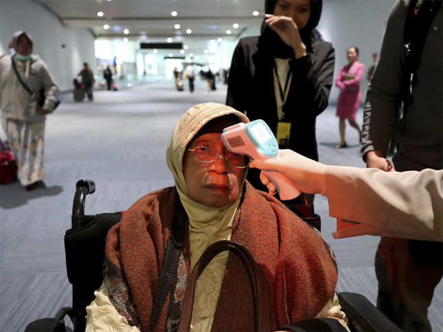 A health official scans the body temperature of a passenger as she arrives at the Soekarno-Hatta International Airport in Tangerang, Indonesia. 