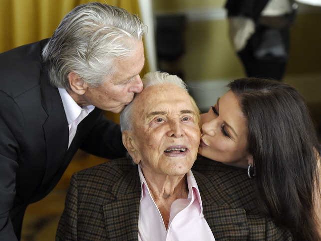 Kirk Douglas (C) gets kisses from son Michael Douglas (L) and daughter-in-law Catherine Zeta-Jones (R) during his 100th birthday party in 2016 .