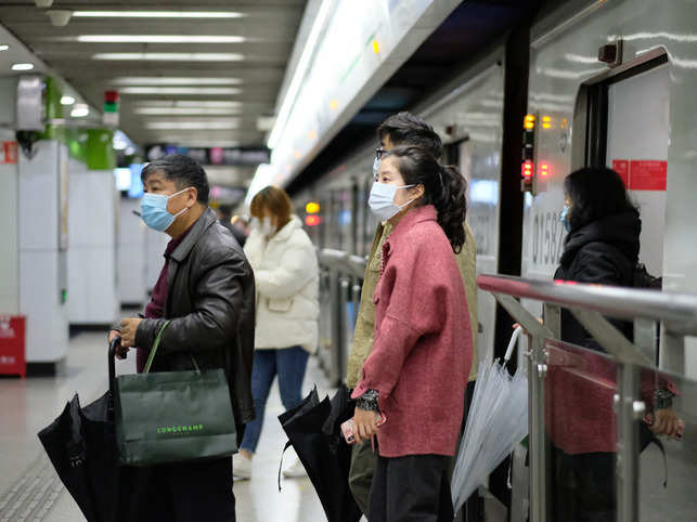 People wearing surgical mask walking out from subway in Shanghai.