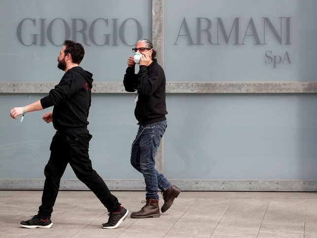 Workers walk past the Giorgio Armani logo outside the theatre where the Italian designer said his Milan Fashion Week show would take place to safeguard the health of press and buyers after a coronavirus outbreak in northern Italy.