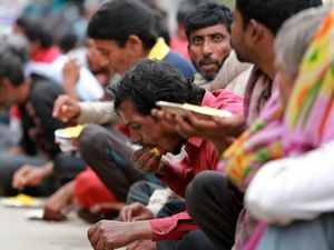 Homeless people eat a meal distributed by the Delhi government. (AP Photo)