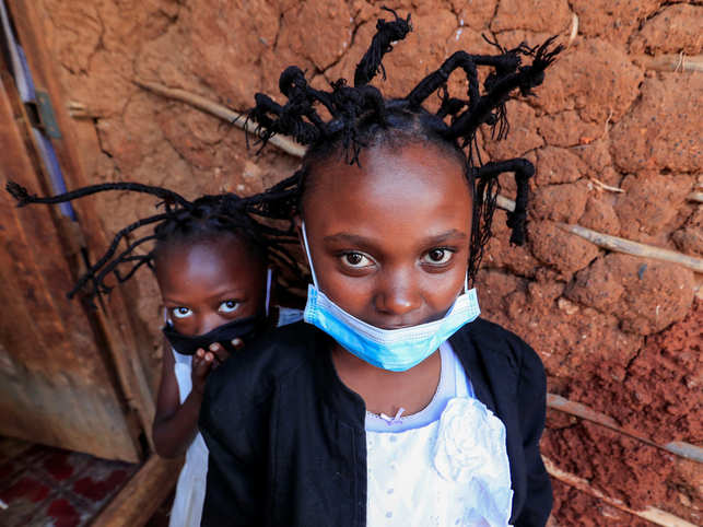 Martha Apisa, 12, and Stacy Ayuma, 8, pose for a photograph outside their house after plaiting with the 'coronavirus' hairstyle, designed to emulate the prickly appearance of the virus under a microscope, as a fashion statement against the spread of the coronavirus disease (COVID-19), at Mama Brayo Beauty Salon within Kambi-Muru village of Kibera slums in Nairobi, Kenya