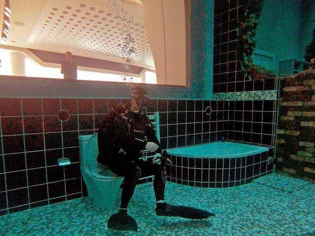 A diver explores a mock sunken city - Dubai does it again: Now world's  deepest pool | The Economic Times